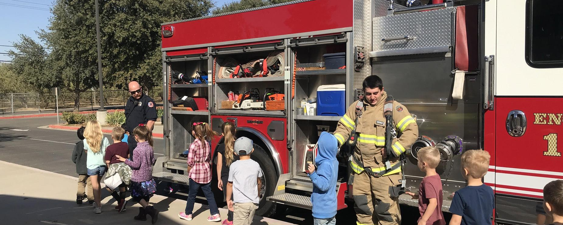 Firefighter high fives kindergarteners