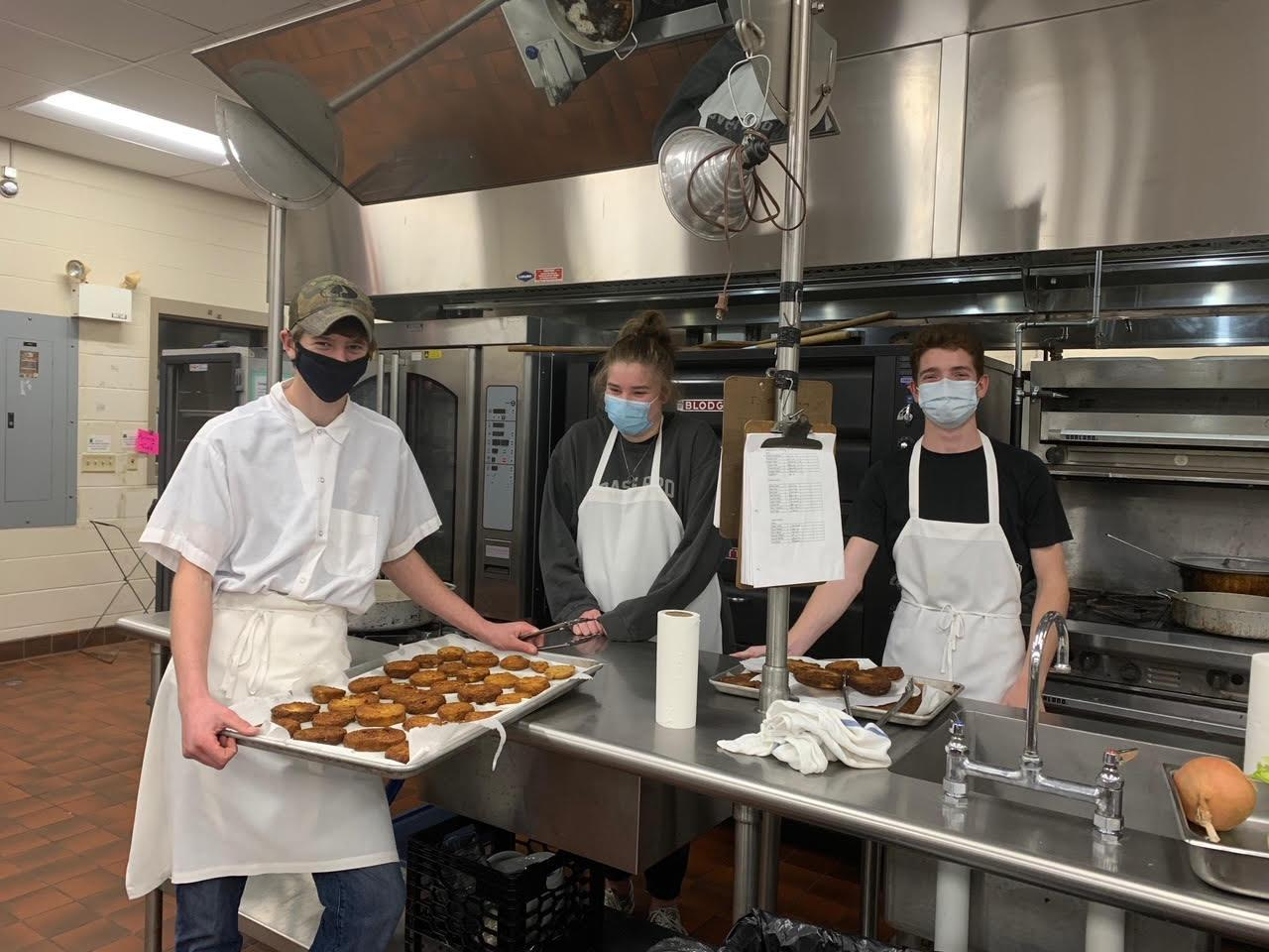 students with food in restaurant kitchen
