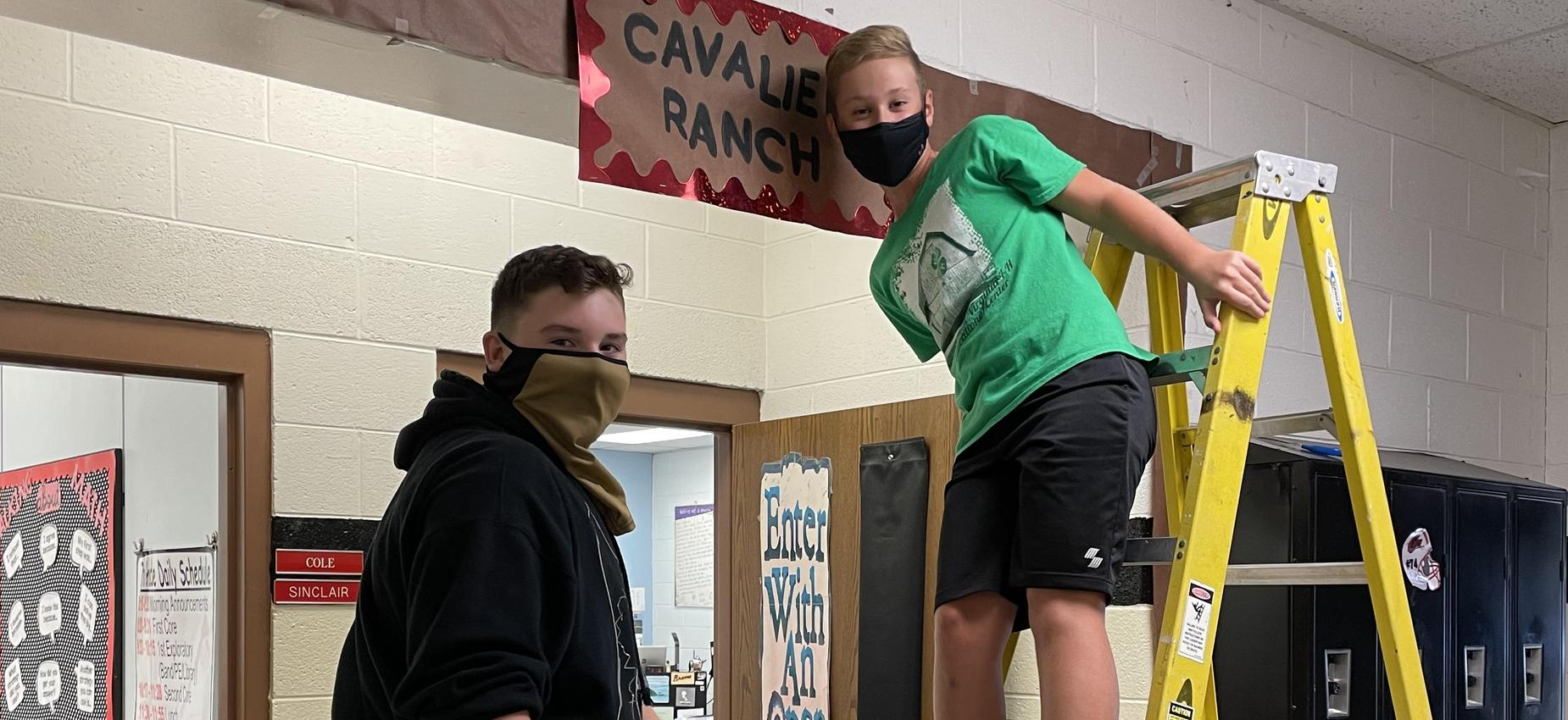 Two students stand on ladders in front of a classroom.
