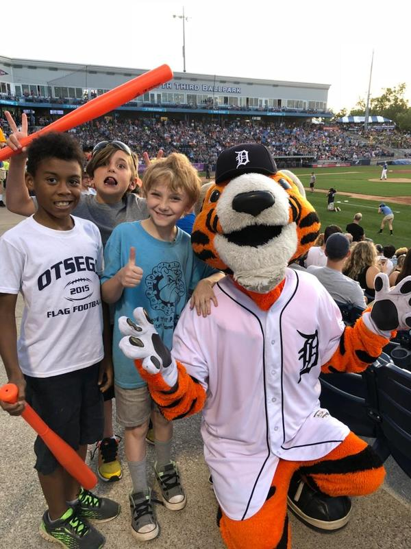 Three kids pose for a picture with the Tiger mascot at the baseball game.