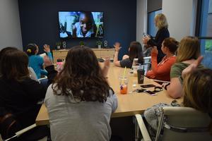 students waving to tv camera