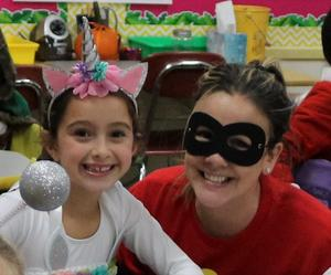 A costumed McKinley 2nd grade teacher and her student smile for the camera as they enjoy a classroom Halloween party.