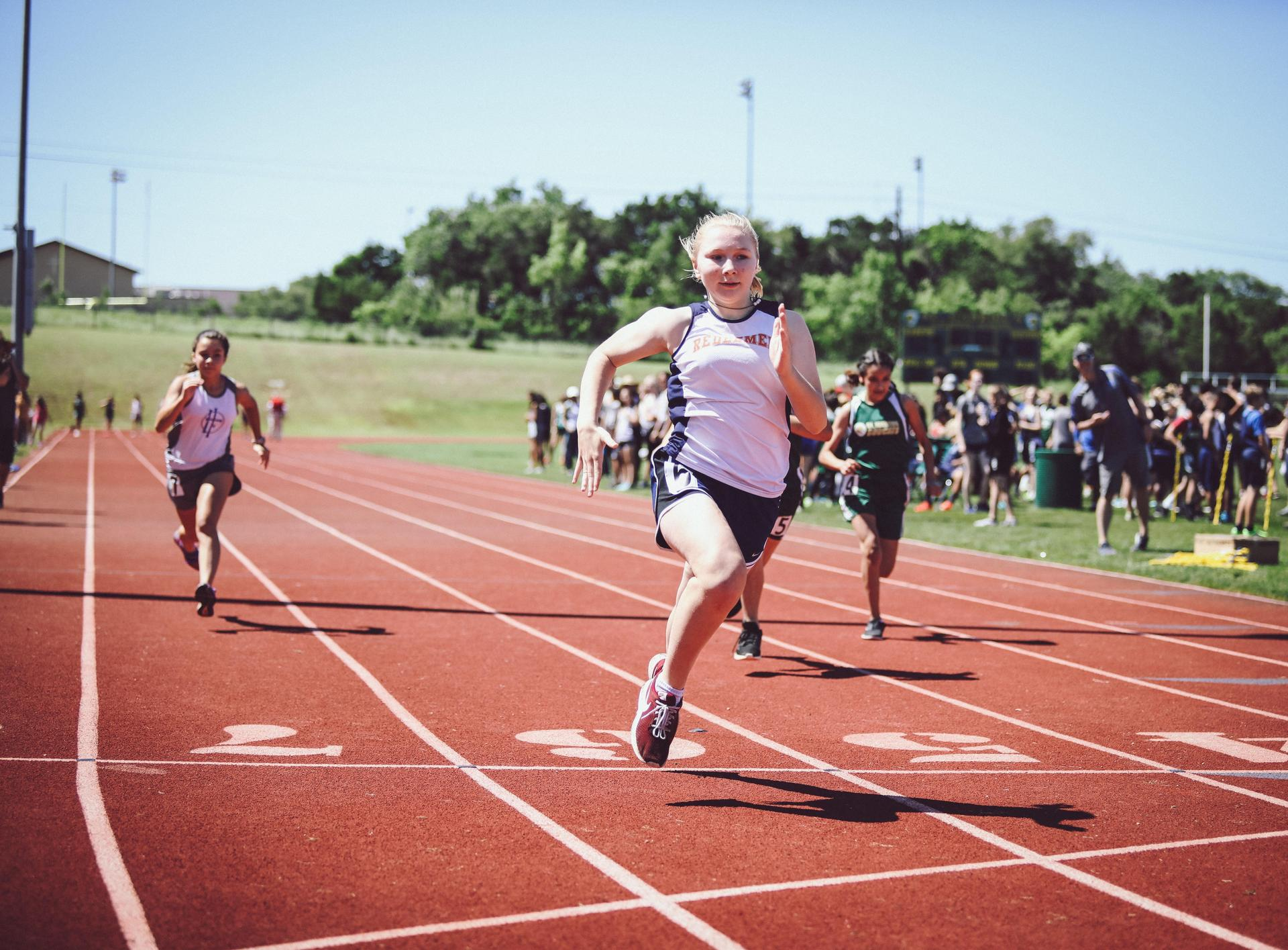 middle school girl running in track meet