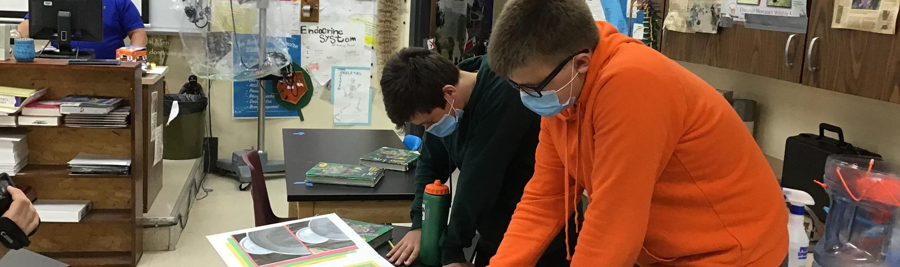 Two students working on a project at their desks