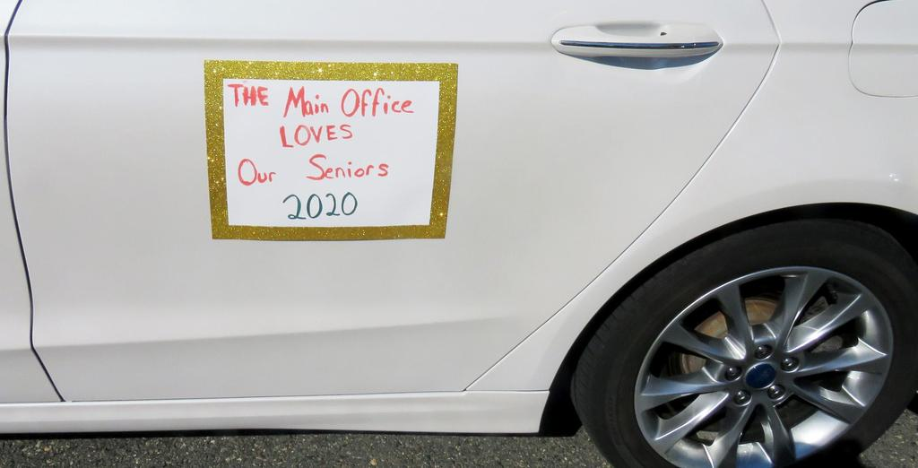 "A sign on a car reading ""The Front Office Loves Our Seniors"""