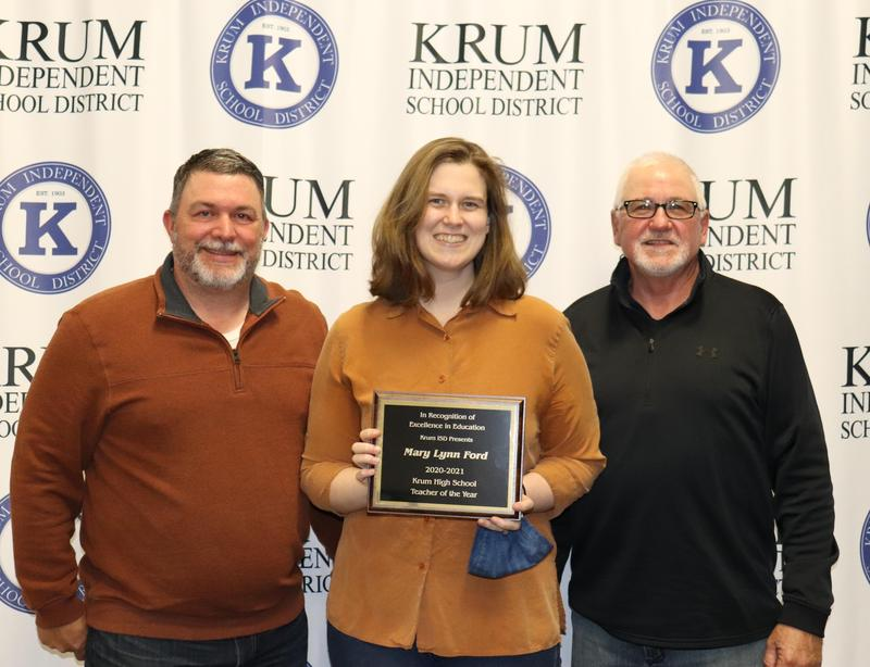 marylynn ford stands with board president eric borchardt and board vp terry knight as they present her with her teacher of the year plaque
