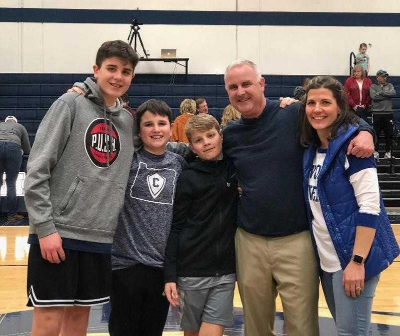five people standing in a gym looking into the camera for a photo