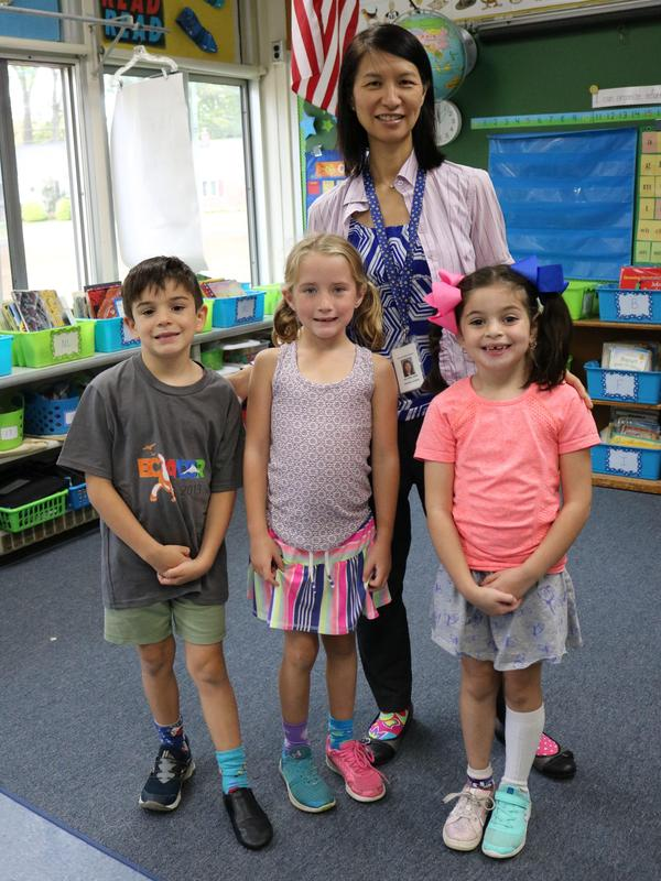 Photo of Jefferson principal Dr. Susie Hung with three students, all wearing mismatched clothing to illustrate how we respect differences.