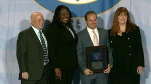 Photo of Washington School principal, 5th grade teacher, and superintendent joining director of National Blue Ribbon Schools program on stage to accept award on behalf of Washington School Community