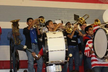 MJHS band students playing wind and percussion instruments at a pep rally.