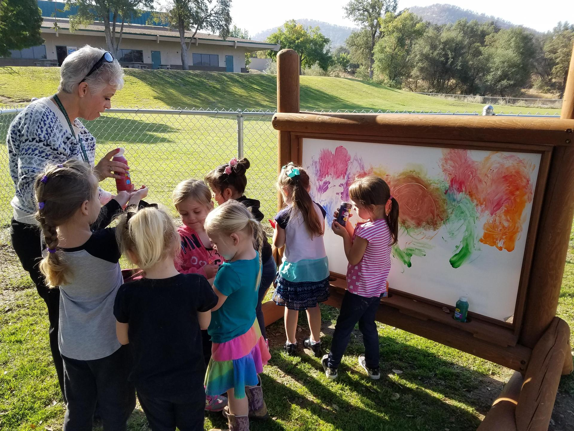 Students painting on outdoor art board