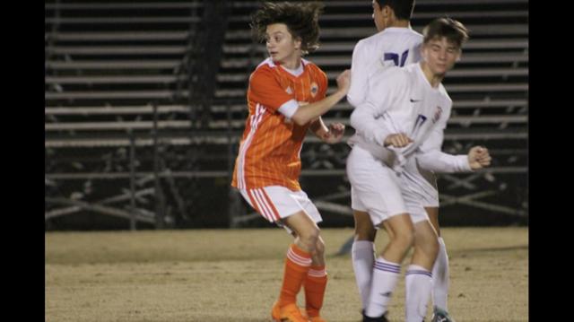 Samuel C. kicking the soccer ball.