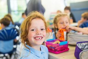Girl with red hair and big smile at a school lunch table