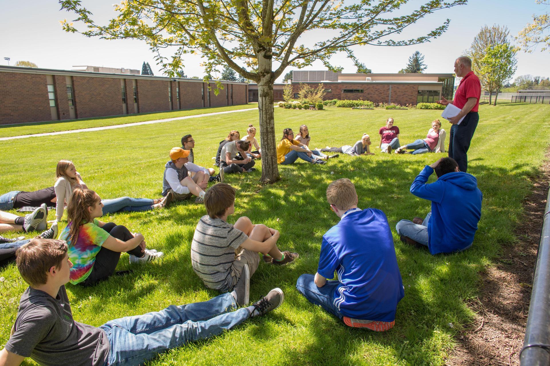 teacher holding class outside under a tree