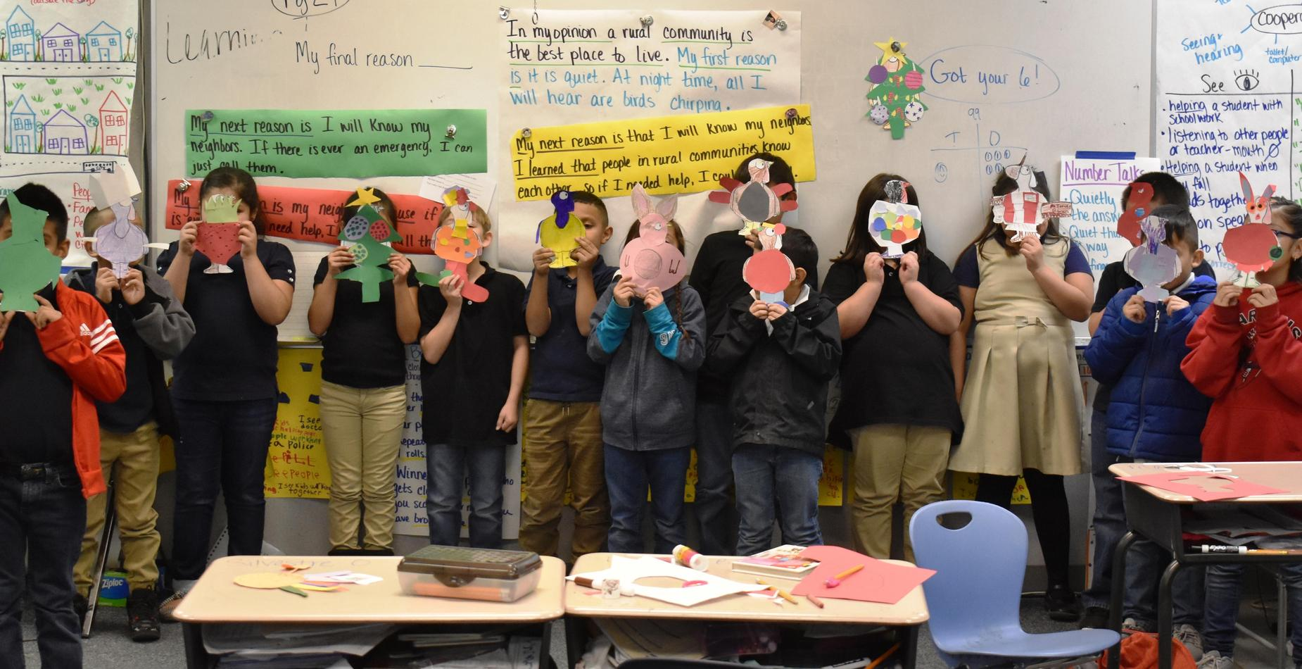 13 students standing in a row with paper turkeys they've disguised in various costumes such as a clown and a bunny rabbit.