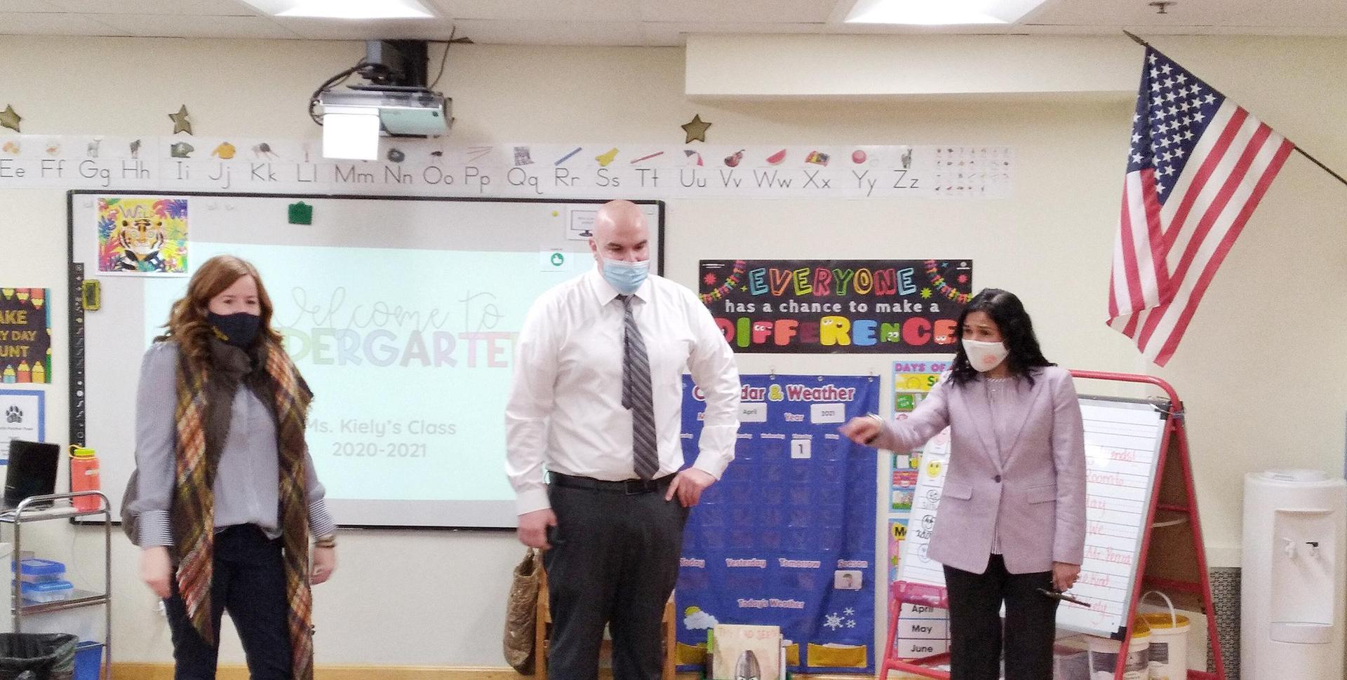 Three educators at the front of a classroom, no students visible