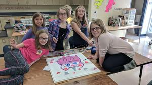 Students paint a unicorn on a ceiling tile
