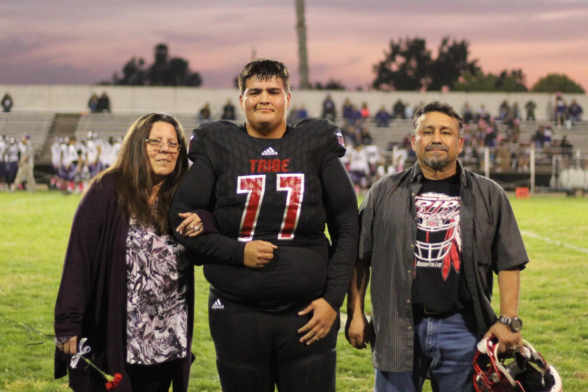Senior football player Daniel Nieves and his escorts.