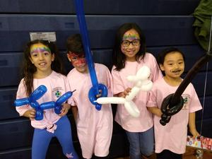 kids with their faced painted holding balloon animals and swords