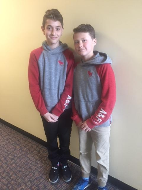 two boys smile in grey sweatshirts with red arms