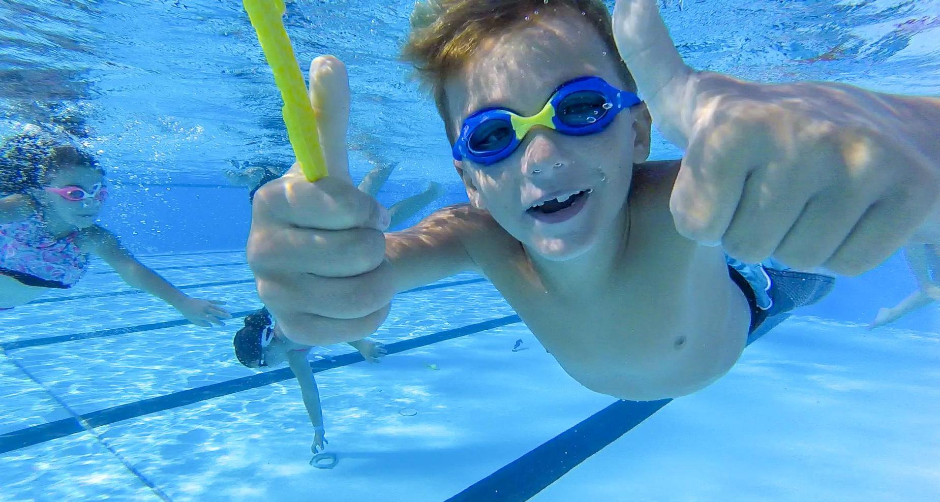 2nd grader showing thumbs up underwater.