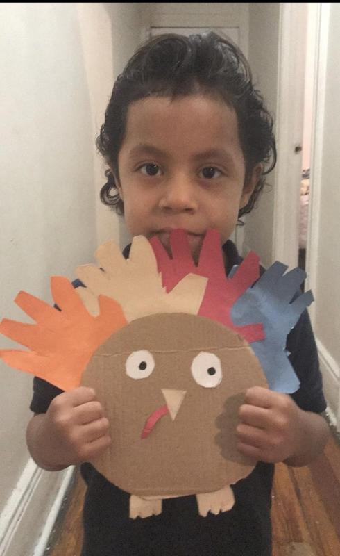Student holding cardboard and hand prints turkey