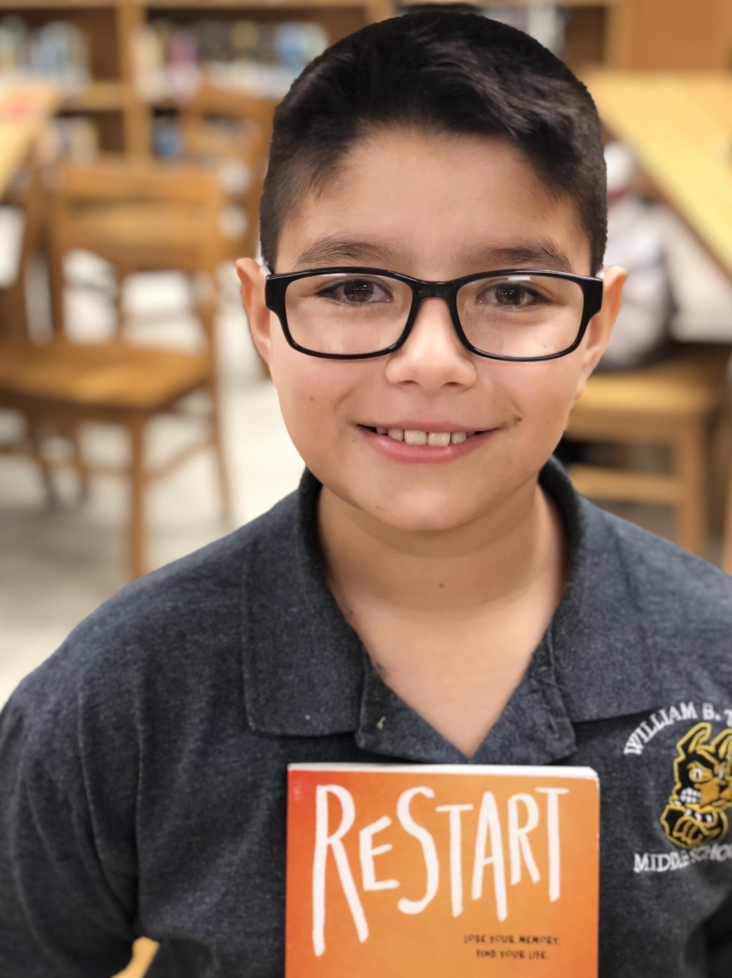 Boy holding a book title.