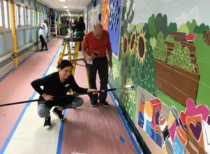 Parent volunteers at Jefferson Elementary School help to transform school hallways into a magical scene of the many events that take place each year.  Parent volunteers are pictured here painting the mural.