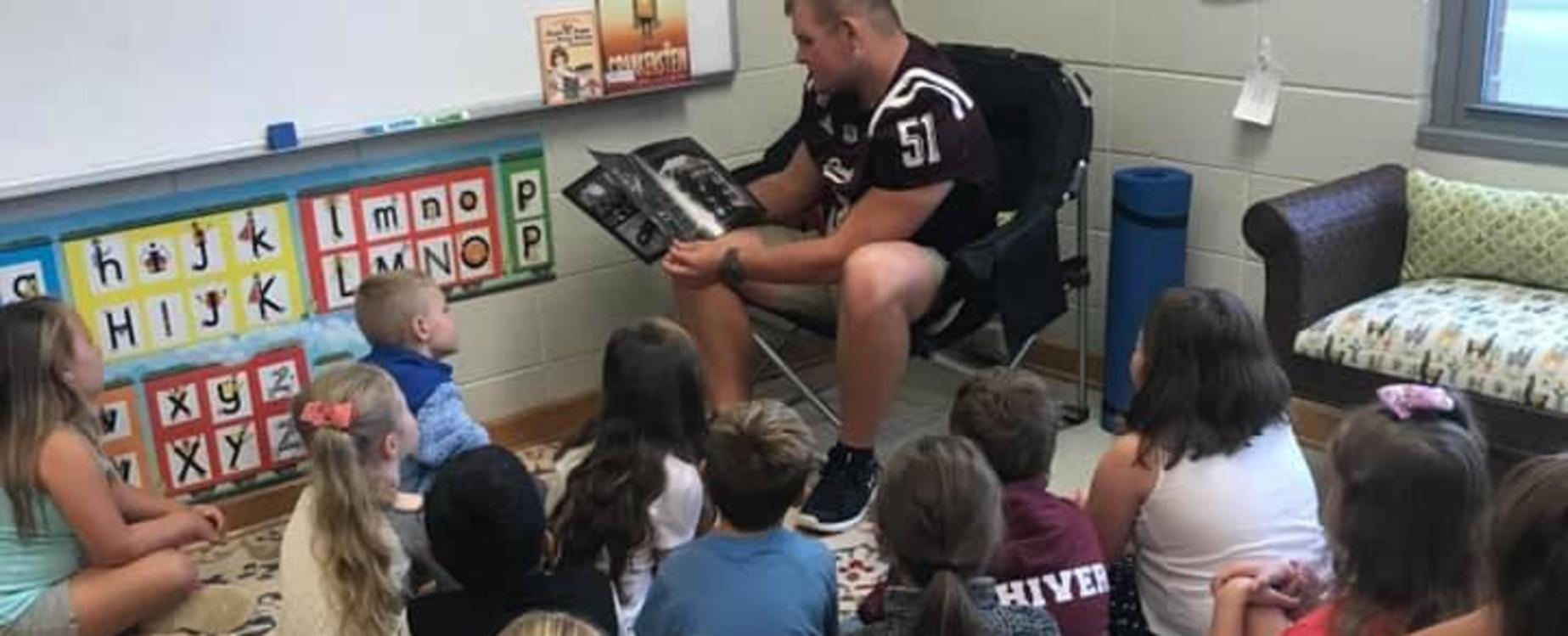 Chase Hughes (#51) reads to our students