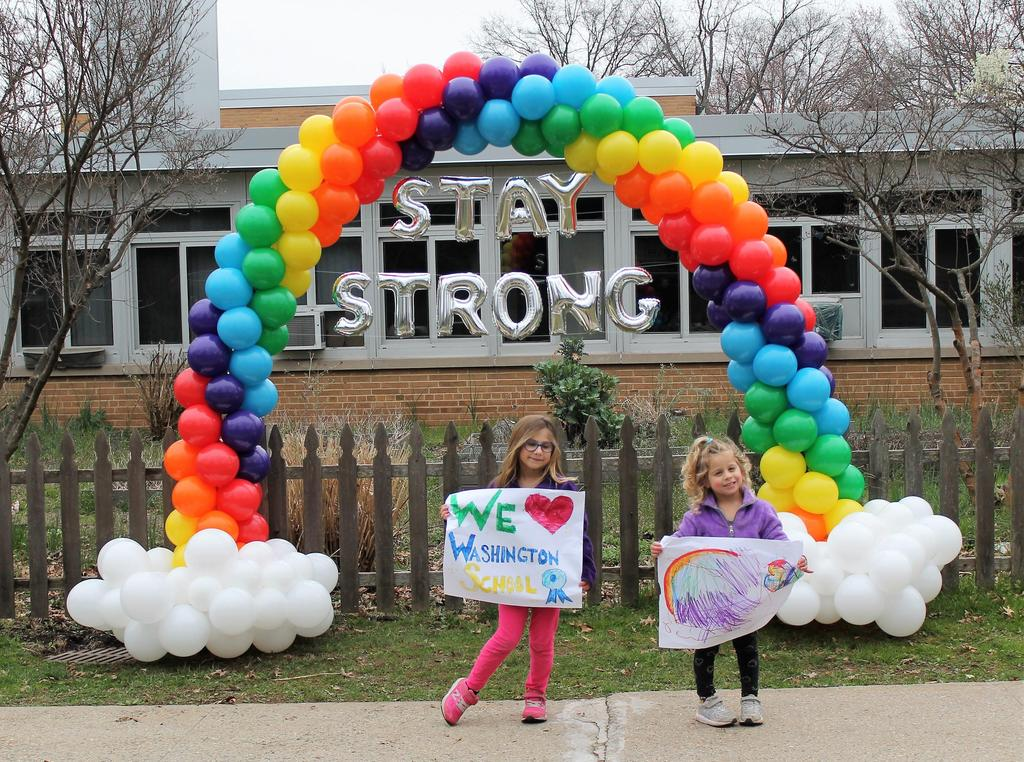 Photo of two Washington students posing in front of rainbow made of balloons.