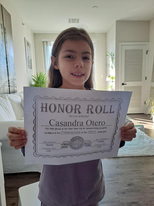 Casandra holding honor roll certificate