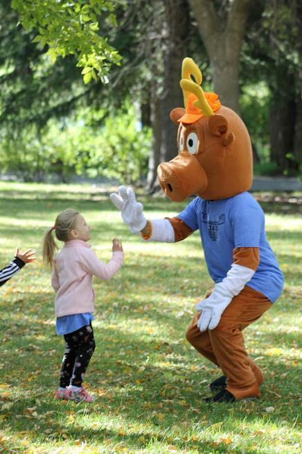 Moose mascot high-fiving a small child
