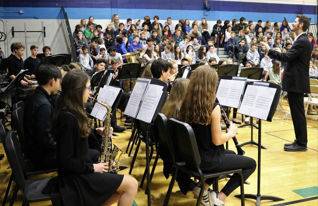 Photo of 8th grade band and band director during Veterans Day assembly.