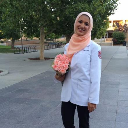 Ruquaya Quraishi smiles while holding bouquet of flowers