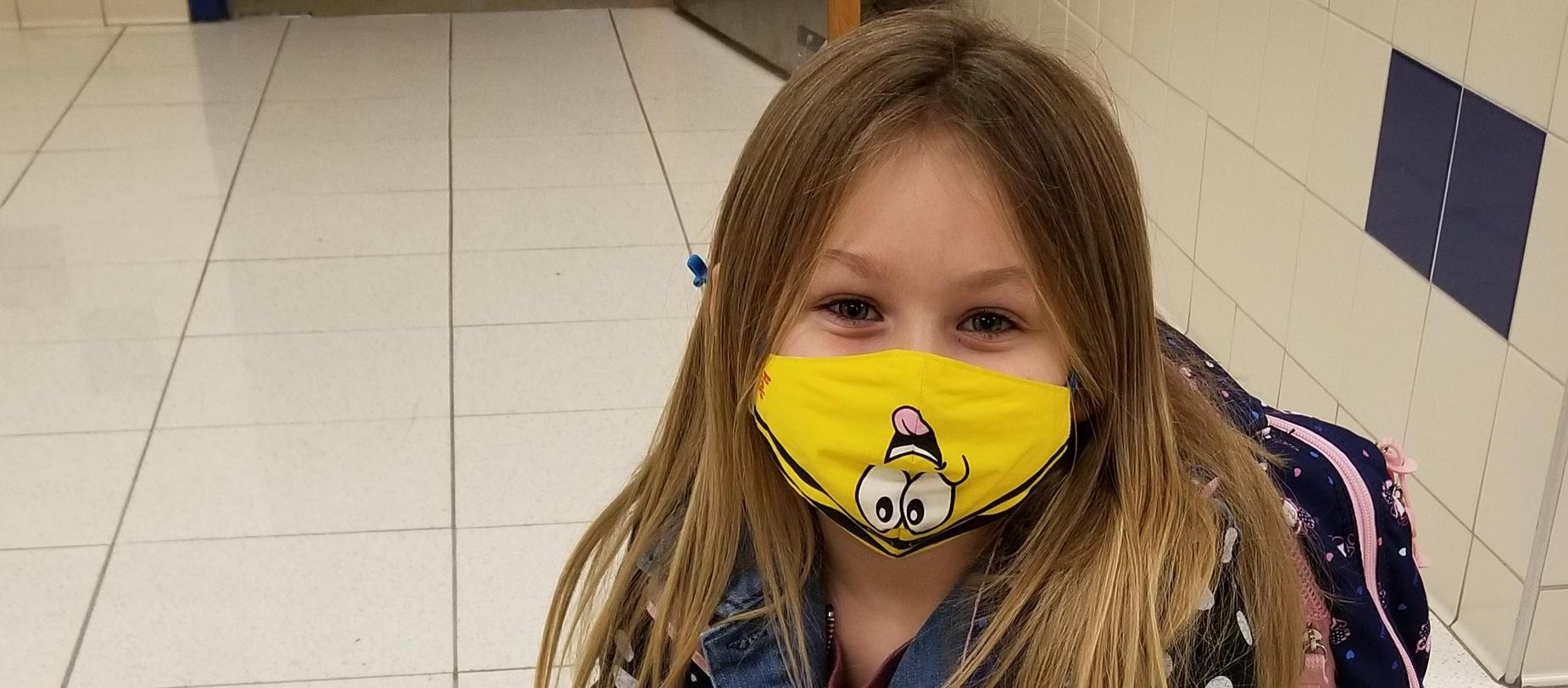 girl wearing a mask posing for the camera