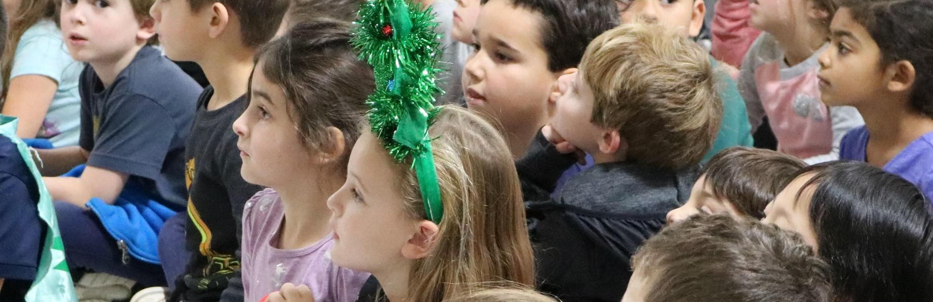 Photo of kindergartners listening to holiday concert; one girl wearing a christmas tree headband.