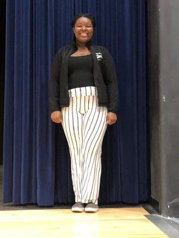 BHS flutist wearing a black shirt and white and black striped pants