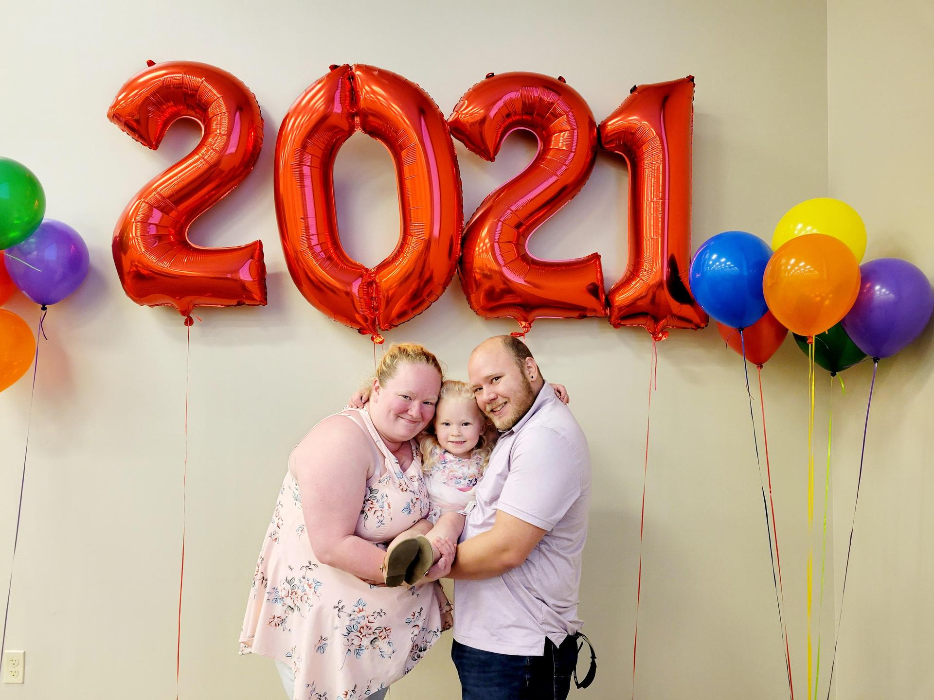 Parents posing for a photo with their daughter in front of 2021 graduation balloon banner