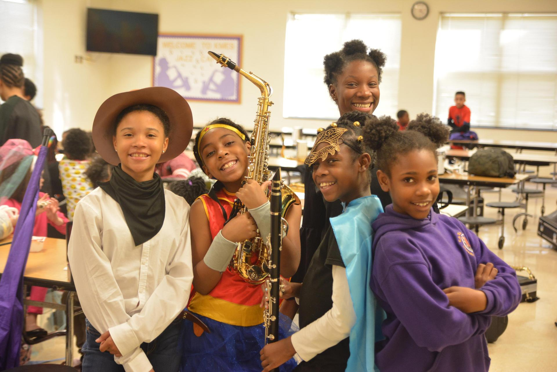 Girls in costumes posing with band instruments.