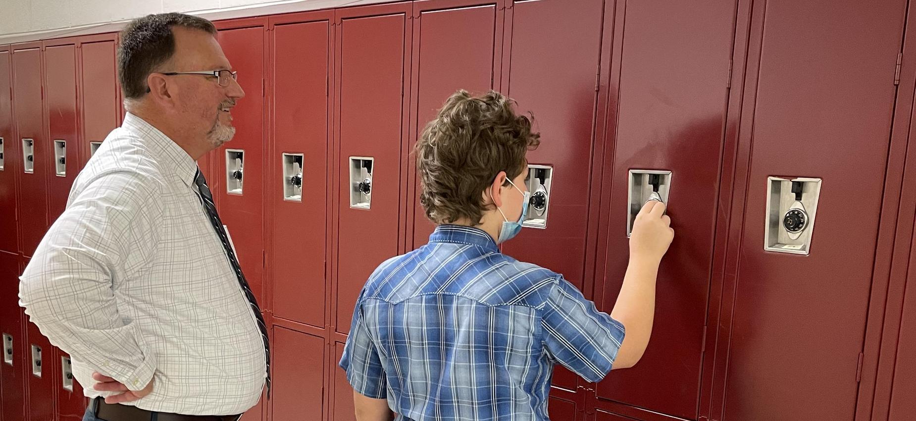 A man watches a student open a locker.