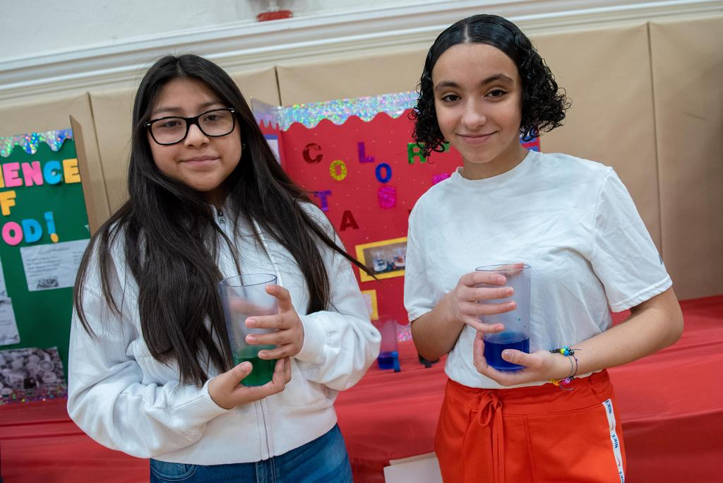 Two students hold liquid-filled jars