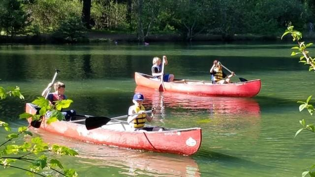 two canoes in lake being rowed by students