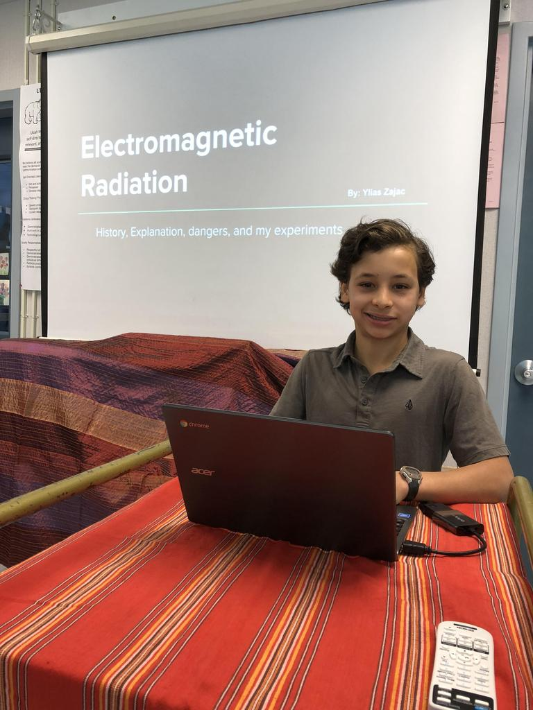 "Student picture with presentation slide ""Electromagnetic Radiation"" in the back"