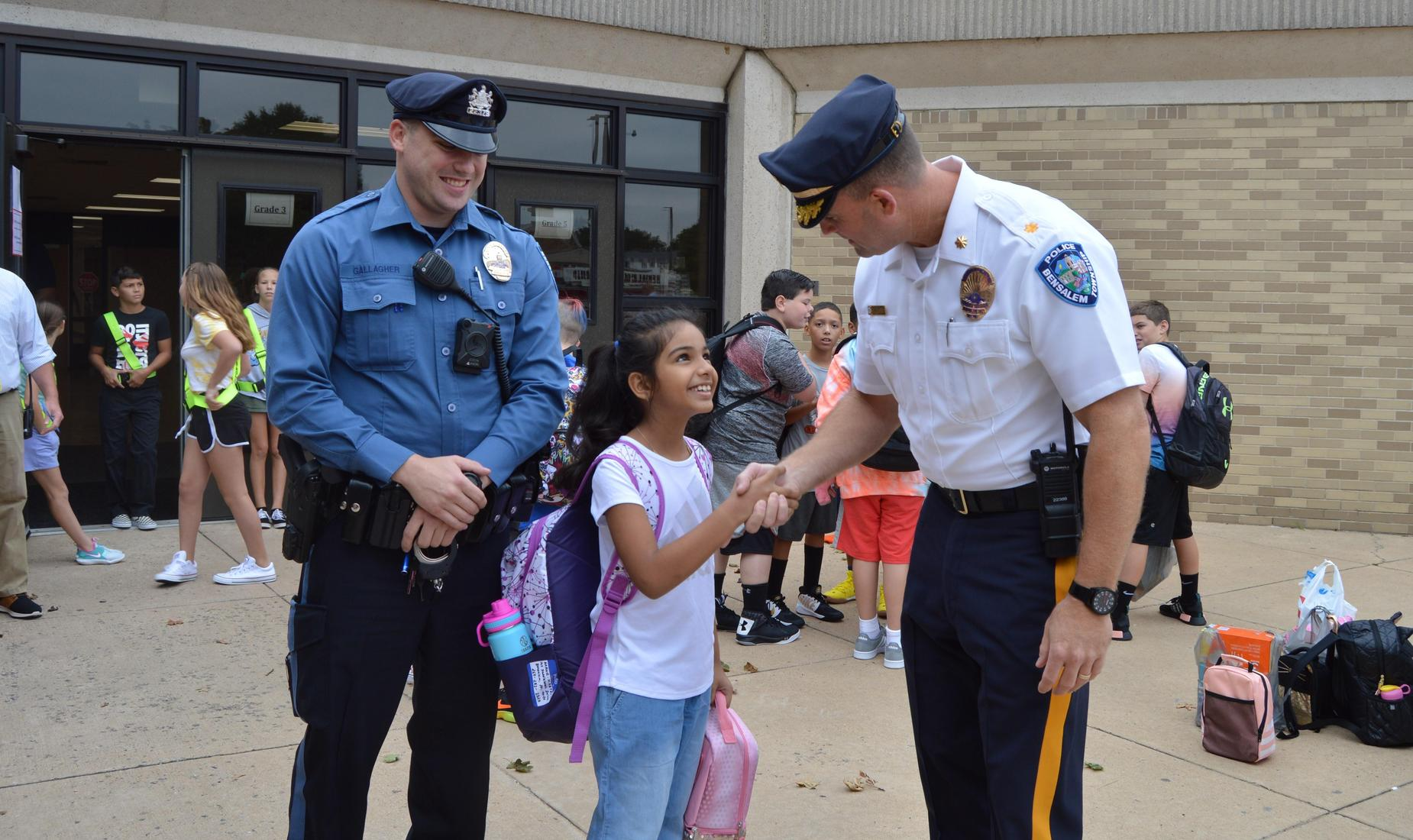 Bensalem Police Sergeant shakes hands with a young female student as a Police officers looks on smiling.
