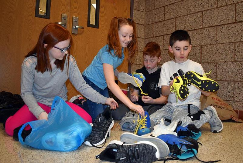 Students gather and sort shoe donations.