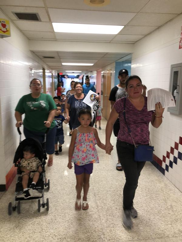 Parents on their way to classrooms in the hall.