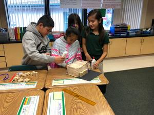 students working together to design and build a structure that can withstand a simulated natural disaster, image 5