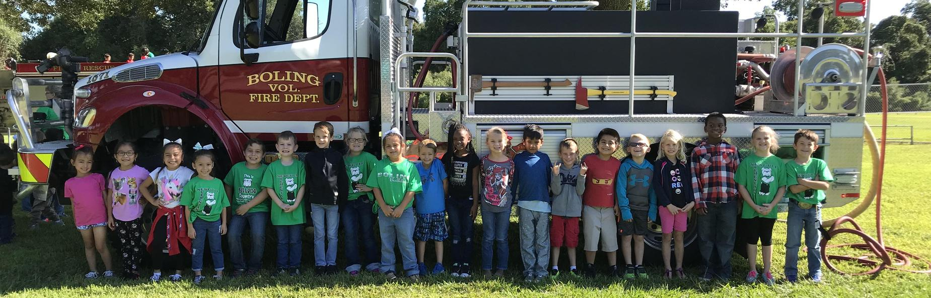elementary school children next to fire truck