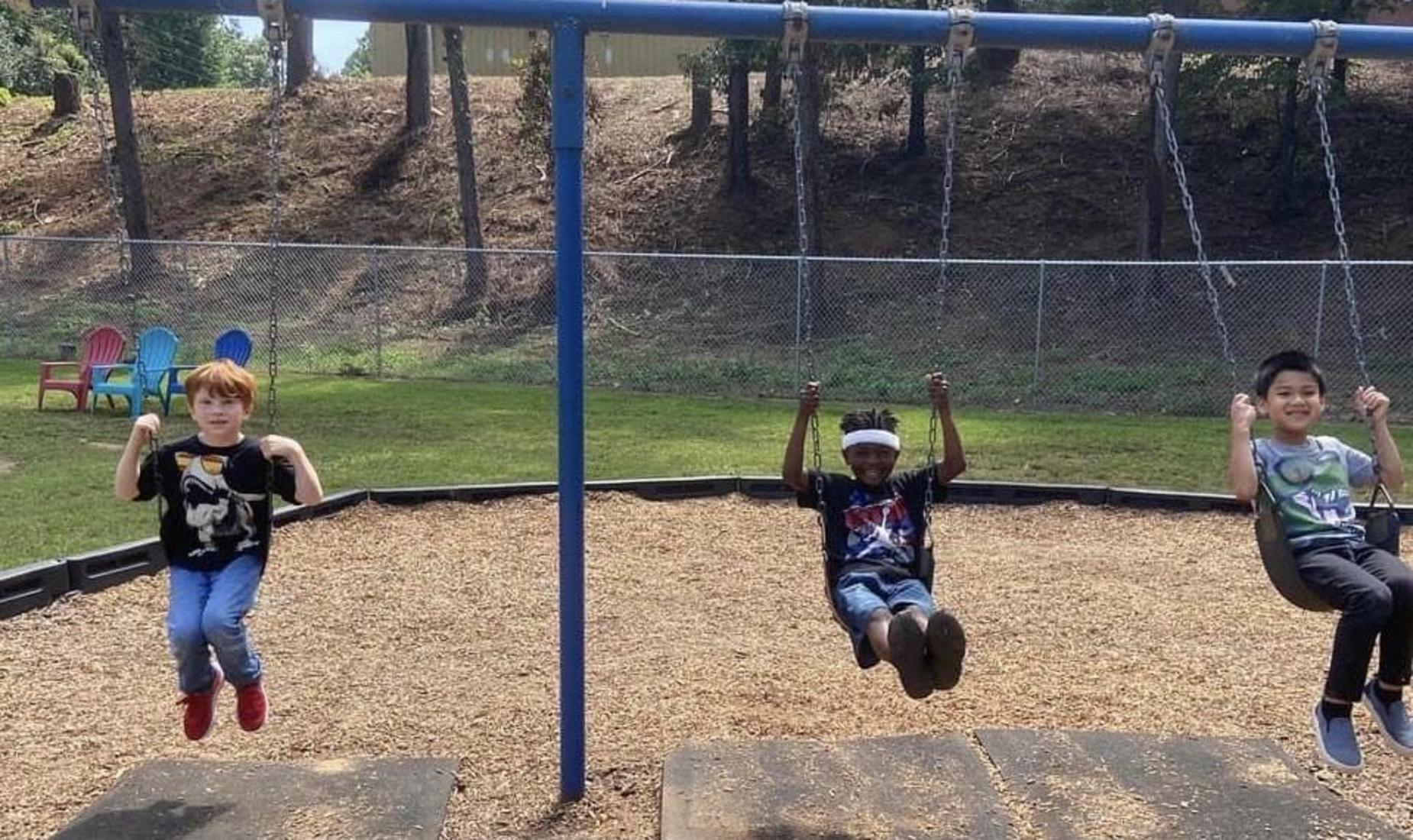 3 kids swinging