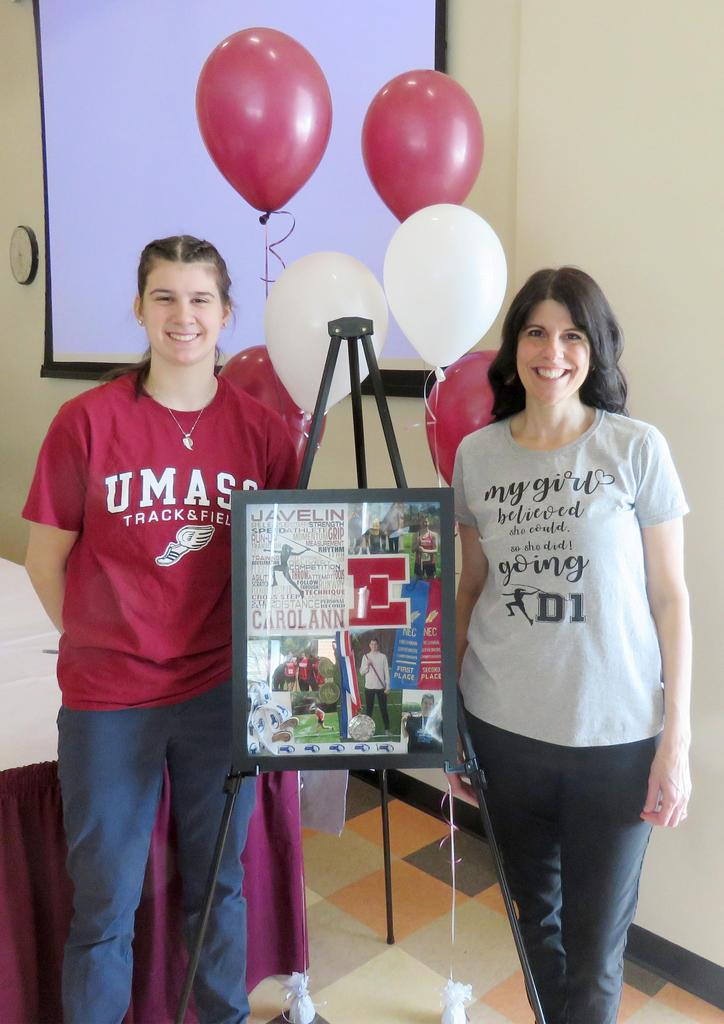 Carolann Cardinale and her mother stand in front of a photo collage and crimson and white balloons